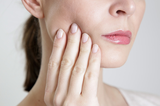 Woman pressing at her aching jaw